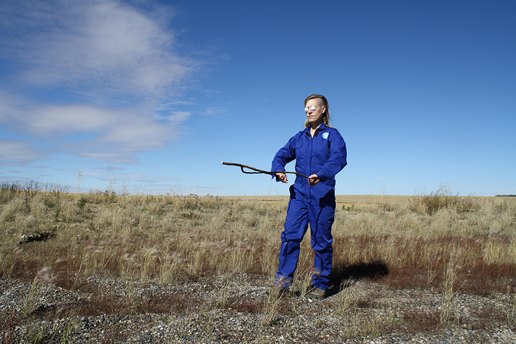 a person in blue coveralls with a divining rod standing in a field with a blue sky