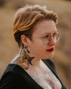 Image of a person with short strawberry blonde hair and glasses standing profile