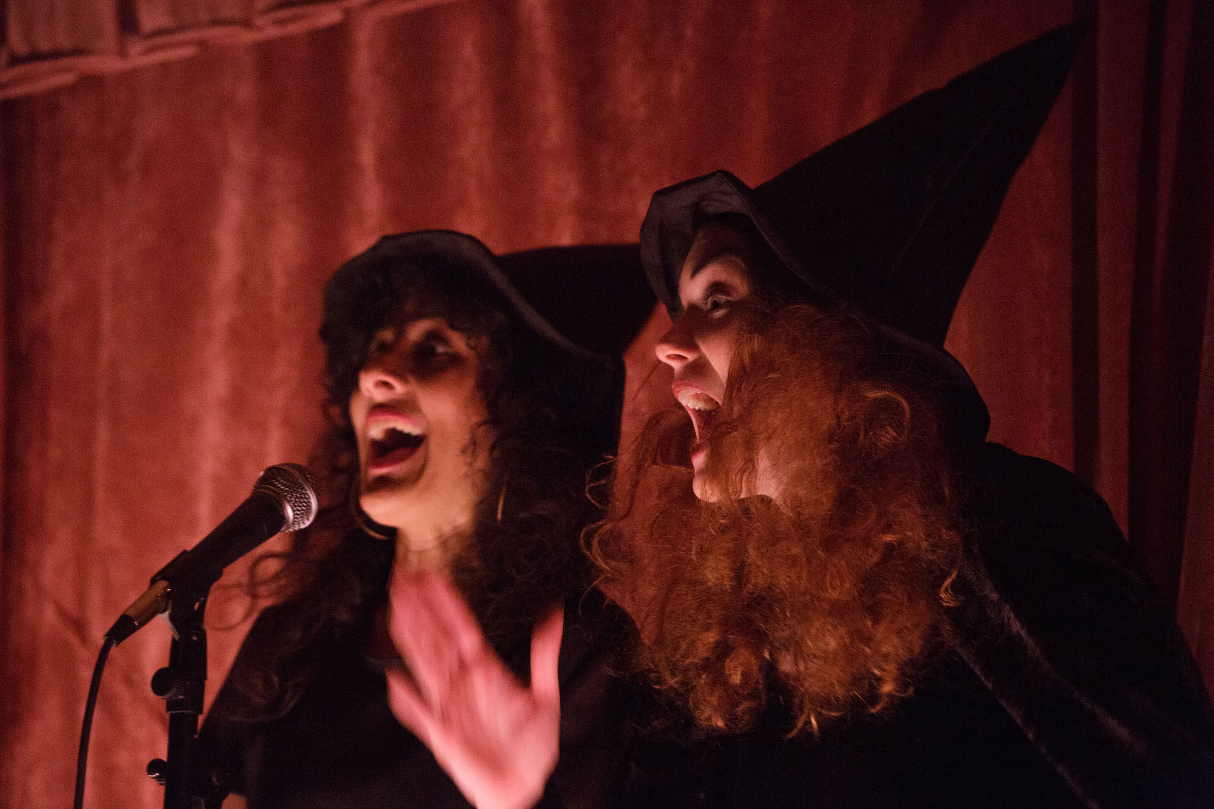 Two people dressed in black pointy hats animatedly speaking into a mic in front of a red curtain