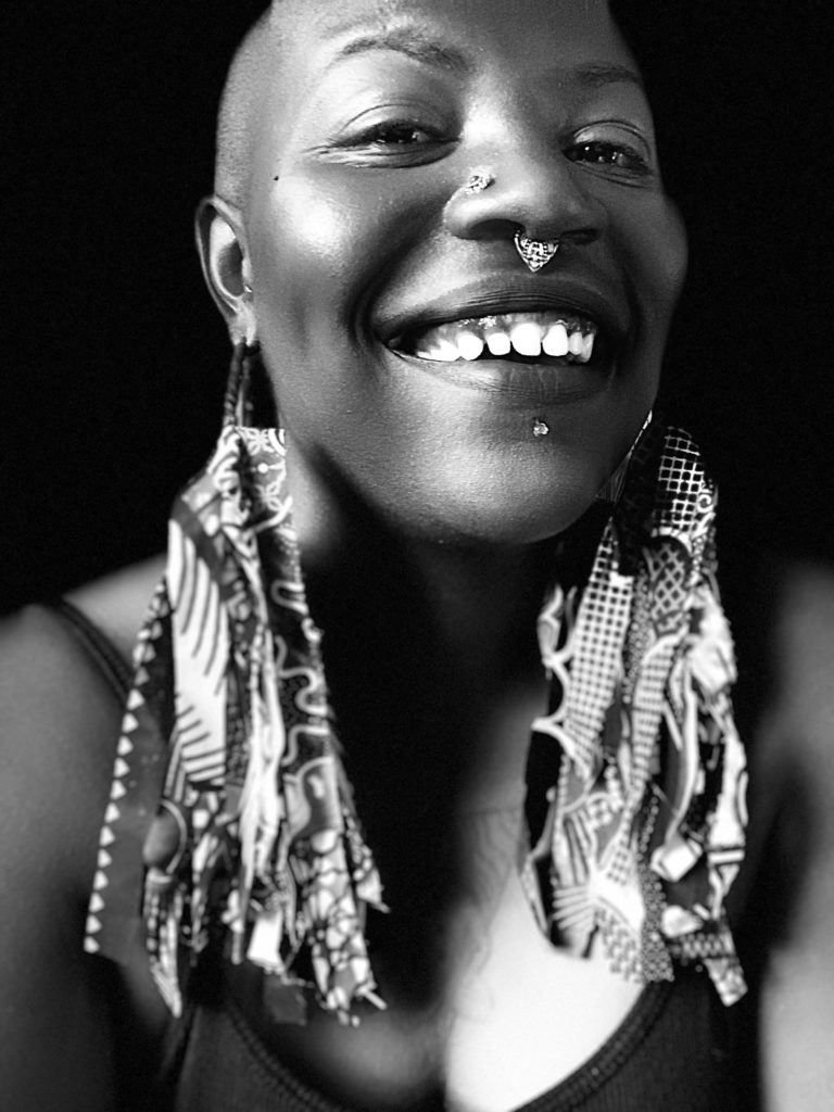 Black and white photo of Goddess Carol wearing large textured earrings and smiling