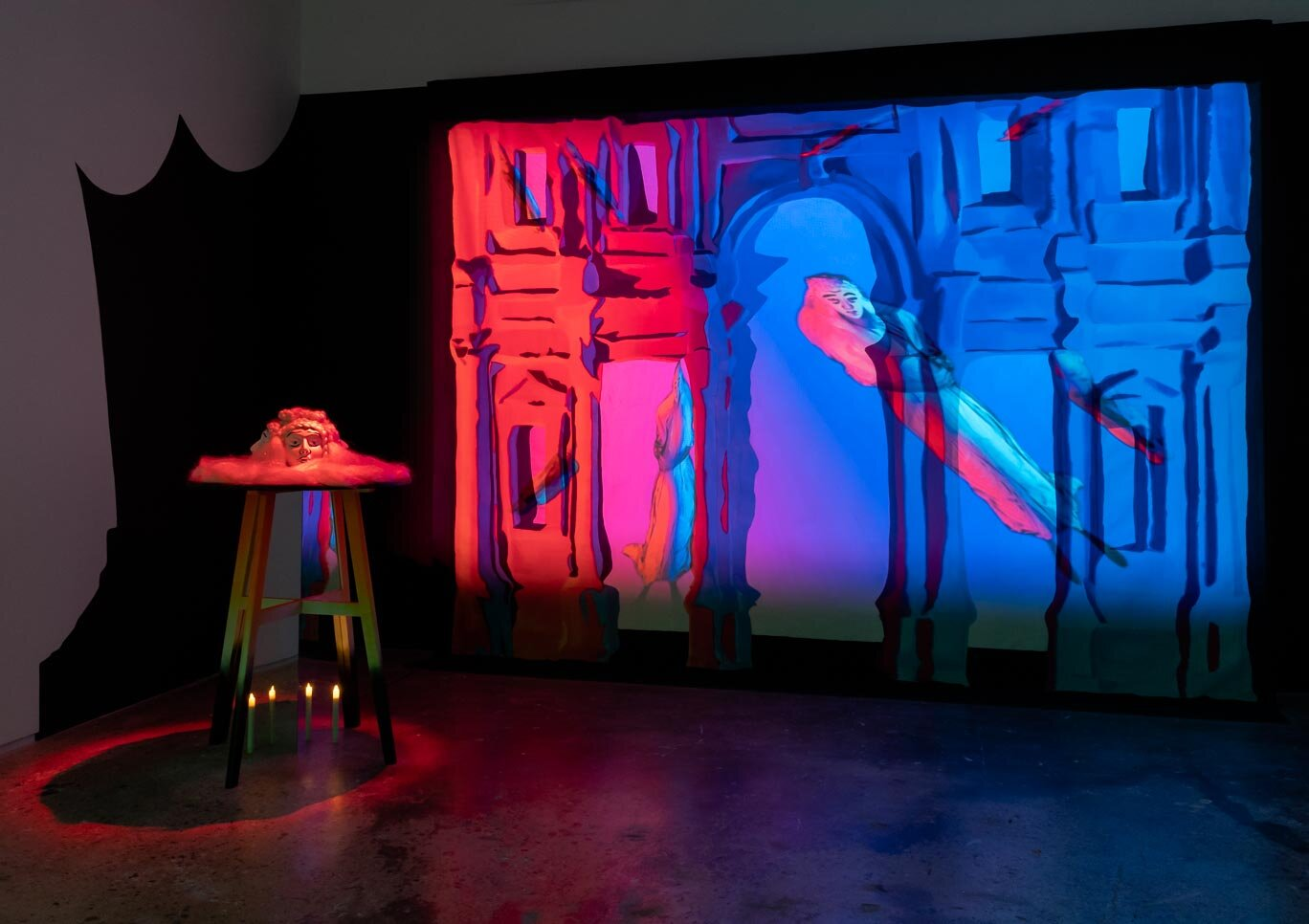 art installation with various layers, appearing like a set with a red and blue light shining on it