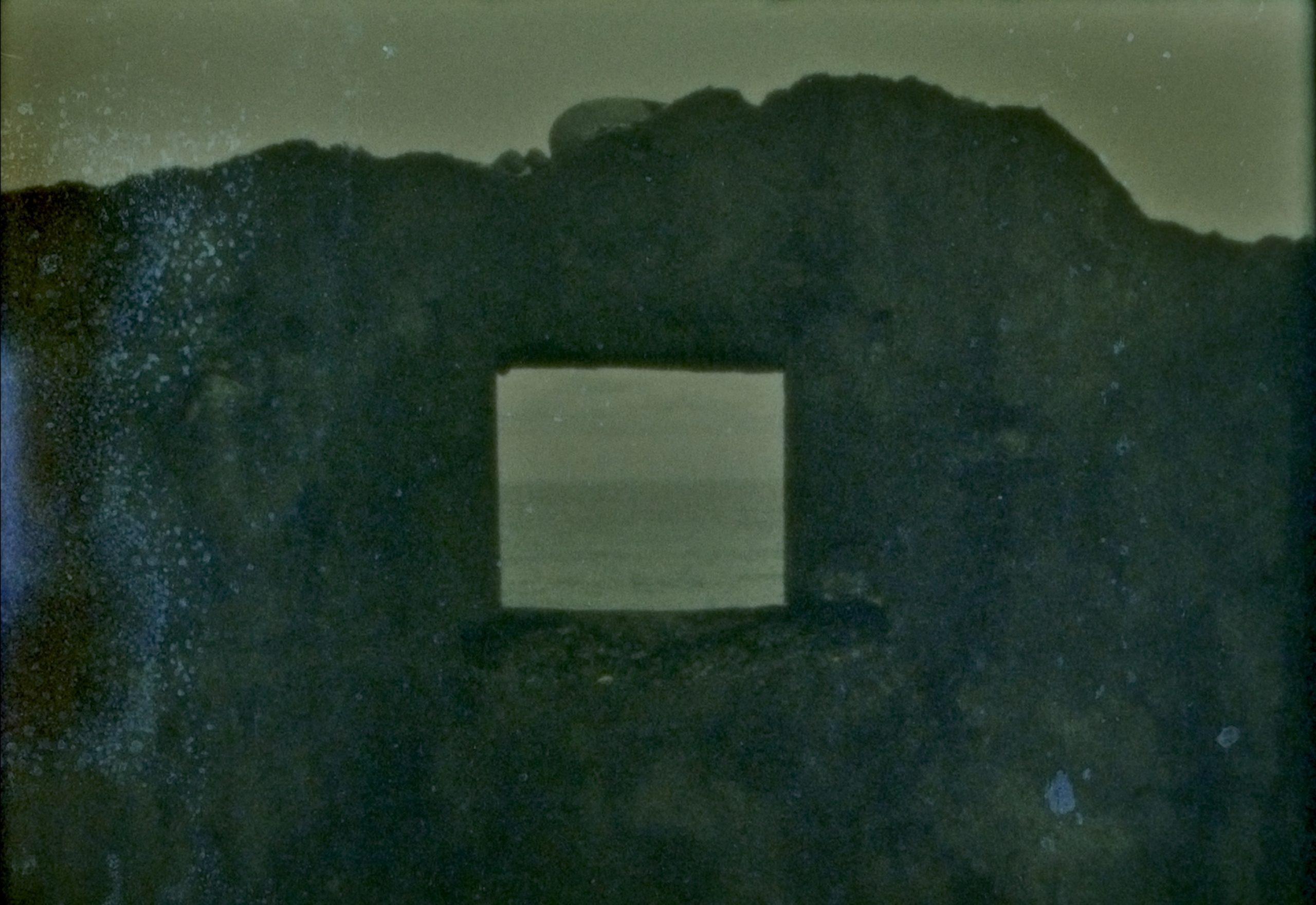 A dark rock like shape with a window hole in it