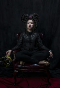 a figure in dark clothing against a black background, sitting is holding a crown