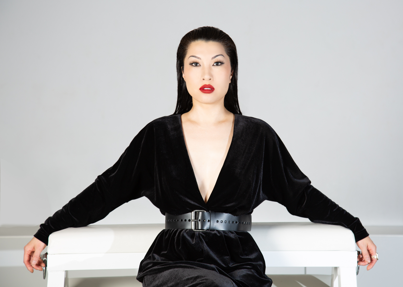 a person wearing a black dress with slicked back black hair seated against a white background