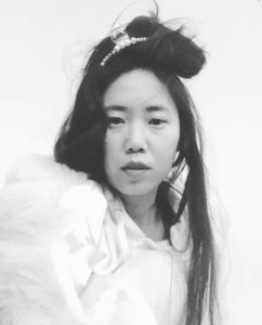 a person in a white dress in a black and white photo with long black hair half tied up with a clip
