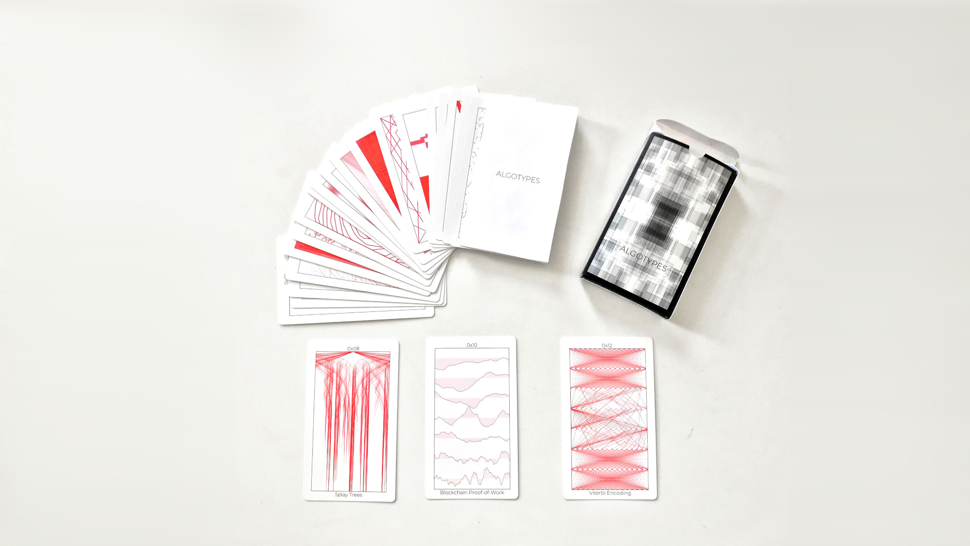 a deck of cards with black and red images on them splayed on a white background