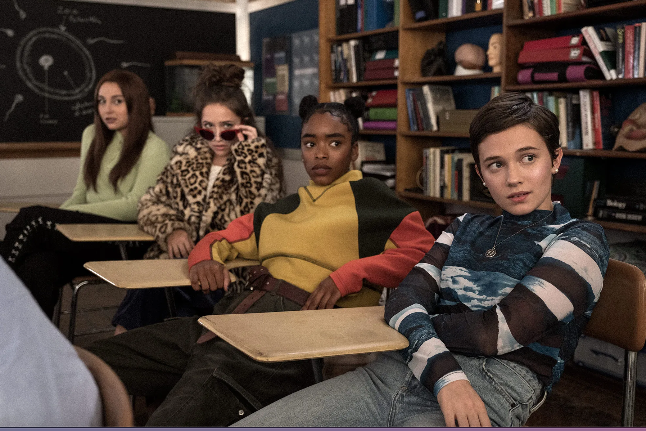 Four young girls sitting at desks in a school, still from the Craft Legacy