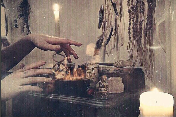 a grainy image of hands above an alter with a candle and feathers and other magical objects