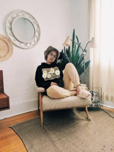 Cassandra lounging on a chair in a neutrally decorated room with a plant, soft light is coming in the window.