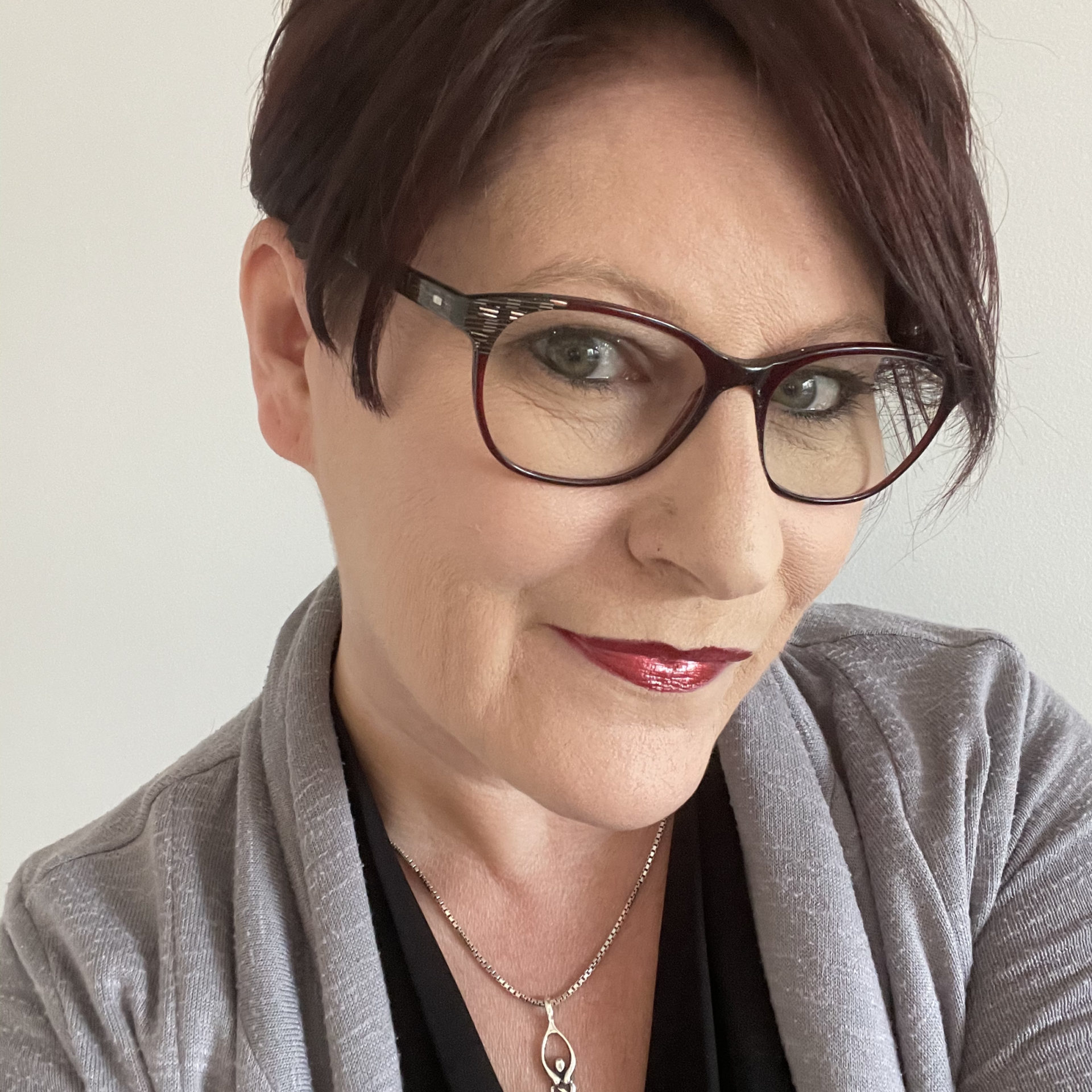 Gina Snooks wearing glasses and a grey cardigan with a black shirt, smiling