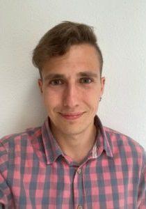 Miguel Sebastian Martin wearing a plaid shirt against a white wall
