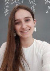 Sara Segura-Arnedo against a dark backdrop smiling, wearing a white shirt